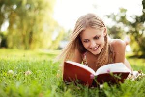 Mujer joven libro de lectura en el parque acostado sobre el césped foto