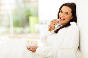 woman eating popcorn on bed