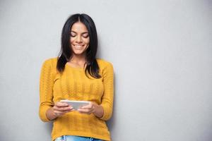 Smiling woman using smartphone photo