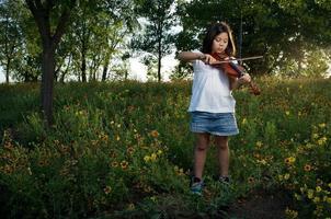 el pequeño violinista entre flores silvestres foto