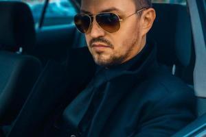 Hombre elegante en traje negro conduciendo coche