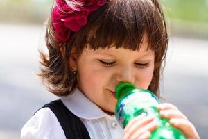Small girl drinking water from bottle