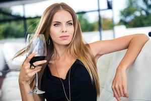 Woman sitting at the restaurant with glass of red wine photo