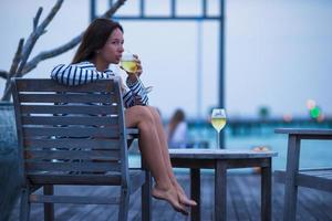 Young girl with white wine at evening outdoor cafe photo