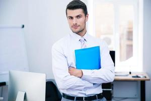 Businessman standing with folder photo