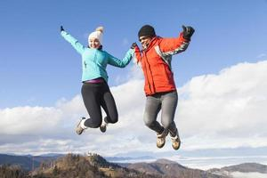 Two happy women jumping outdoors photo