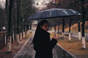 mujer solitaria camina con un paraguas bajo la lluvia foto