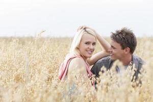Porträt der schönen jungen Frau, die mit Freund inmitten des Feldes sitzt