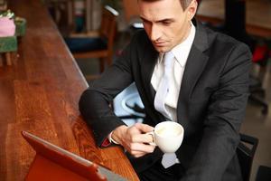 empresario tomando café y leyendo noticias foto
