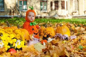 enfant en costume de citrouille sur fond de feuilles d'automne