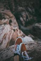 Close-up of low-top sneakers near a cliff