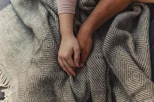 People holding hands on top of blanket photo