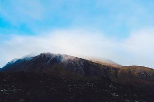 Misty mountain under clear blue sky