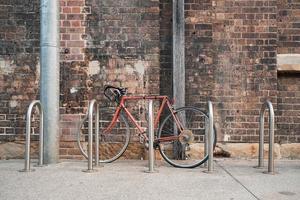 Red bike next to bike rack near wall
