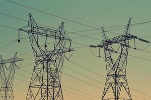 torres de transmisión negras bajo un cielo verde