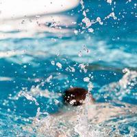 salpicos de água de uma pessoa que salta na piscina foto