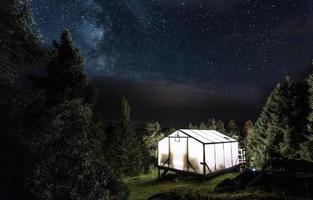 Refugio de campamento iluminado bajo el cielo estrellado.