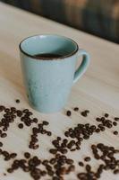 taza de café azul con granos de café