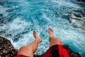 Person, die auf Klippe nahe Wasser sitzt foto