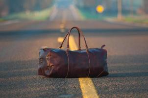 Brown leather duffel bag in middle of asphalt road
