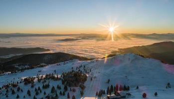 el sol se eleva sobre el paisaje de montaña foto