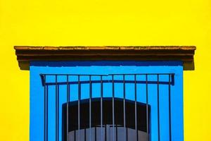 Blue caged window on yellow wall