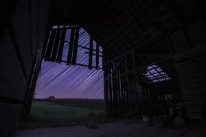 Star trails in a wooden barn at night
