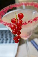 Working at home with currants cocktail and laptop