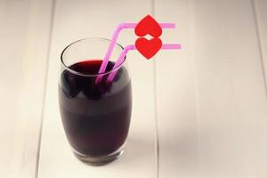Cherry juice glass with red hearts as a kissing lips