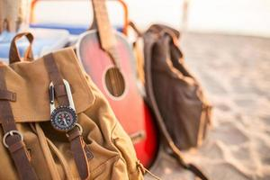 Backpack on the beach with compass and guitar.