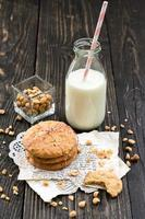 Peanut butter cookies, milk and peanuts on a wood surface