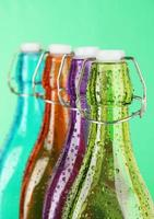 botellas de colores sobre fondo verde foto