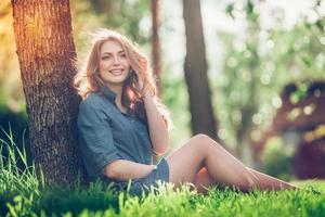 Pretty young caucasian woman  sitting outside under a tree talking