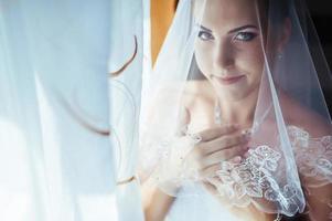 hermosa novia preparándose en vestido de novia blanco con peinado