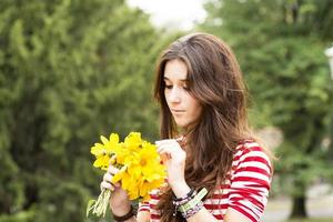 hermosa mujer romántica con ramo de flores en el parque.