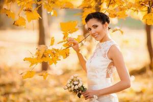 Happy bride in autumn park. Smiling girl in white dress