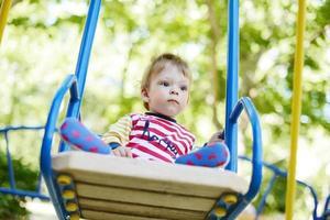 cute little boy riding on a swing photo