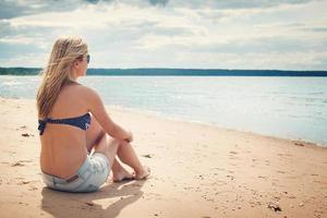 woman sitting on the beach in sunglasses photo