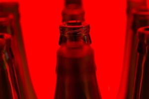 Ten green bottles in three rows shot with red light. photo