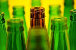 Diez botellas de cerveza vacías sobre un fondo amarillo foto