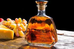Botella de whisky en la mesa con queso y uvas foto