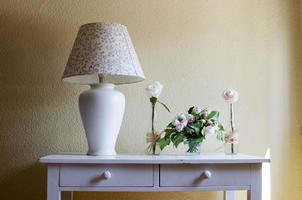 vintage corner with lamp, vase of flowers and white roses photo
