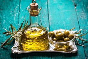 Olive oil and olives on wooden table photo