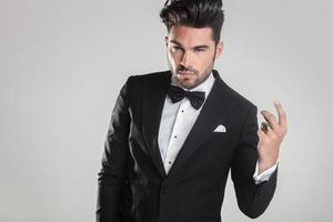 handsome young man in tuxedo snapping his finger