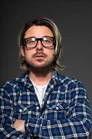 joven con cabello rubio y barba con gafas retro.
