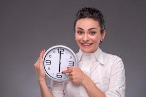 Retrato de niña bonita con gran reloj en sus manos foto