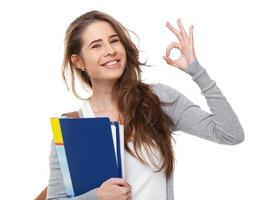 jeune étudiant heureux montrant signe ok isolé sur blanc.