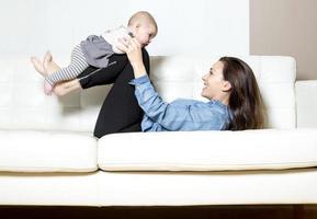 mãe com bebê no sofá se divertindo
