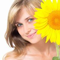 Cute girl peeking out from behind a flower of sunflower photo