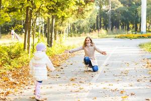 happy family mother and  little daughter playing on autumn walk photo